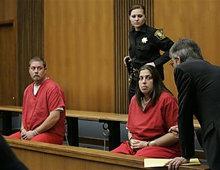 In this Dec. 4, 2008 file photo, Kelly Layne Lau, 30, and her husband Michael Schumacher, 34, appear in a Stockton, Calif., courtroom. Schumacher and Lau stand accused of more than a dozen charges, including torture, kidnapping and child abuse. The alleged abuse of the 16-year-old boy who had escaped from a group home occurred in a well-maintained, two-story Tudor-style house with wreaths on the front door and a Christmas tree in the window. (AP Photo/Paul Sakuma, File)