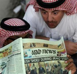 "Saudi men read an English-language Saudi newspaper with the headline ""Bush 'shoed' during Iraq visit"" on Tahleh street in"