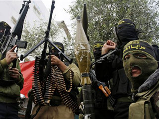 Masked Palestinian militants hold their weapons during an Islamic Jihad rally in Bureij, central Gaza Strip.