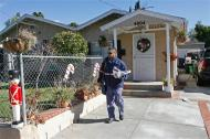 Letter carrier Ray Mayland delivers mail to the home of deceased murder suspect Bruce Pardo, Friday, Dec. 26, 2008, in Montrose, Calif. A ninth body was found Friday morning at the charred site of a Christmas Eve massacre where Pardo, who showed up dressed as Santa Claus at his ex-wife's parents' party, killed at least nine people before setting the home on fire and later killing himself.