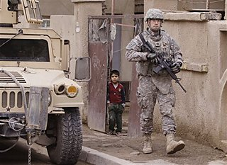 An Iraqi boy looks out of his gate as a U.S. soldier walks by during a routine patrol in Baghdad, Iraq, Tuesday, Dec. 23, 2008. (AP Photo/Karim Kadim)