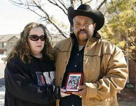 Crystal Franklin, left, mother-in-law of murder victim Summer Garas, and husband James Franklin hold a photo of the slain family outside the victims' apartment in El Reno, Okla. A manhunt is under way for Joshua Steven Durcho, 25, suspected of killing a mother and her four children.