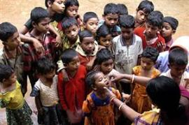 A health worker administers an oral polio vaccine to children in Bhubaneswar, India