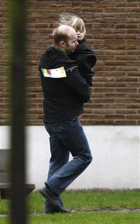 A man carries his child as he leaves a building where families received assistance near the scene of a knife attack at a creche in Dendermonde January 23, 2009.