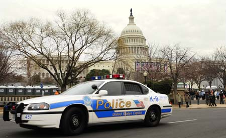 A police car patrols on the street in front of the Capitol building in Washington Jan. 18, 2009. U.S. authorities are tightening up security in the capital city ahead of the Jan. 20 inauguration of President-elect Barack Obama