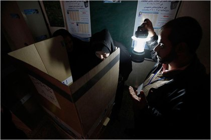An election official held a lantern as a woman voted in Baghdad. Secular parties are hoping that they will be able to capitalize on a protest vote against religious parties amid widespread criticism of their failure to provide jobs, services and utilities since 2005.